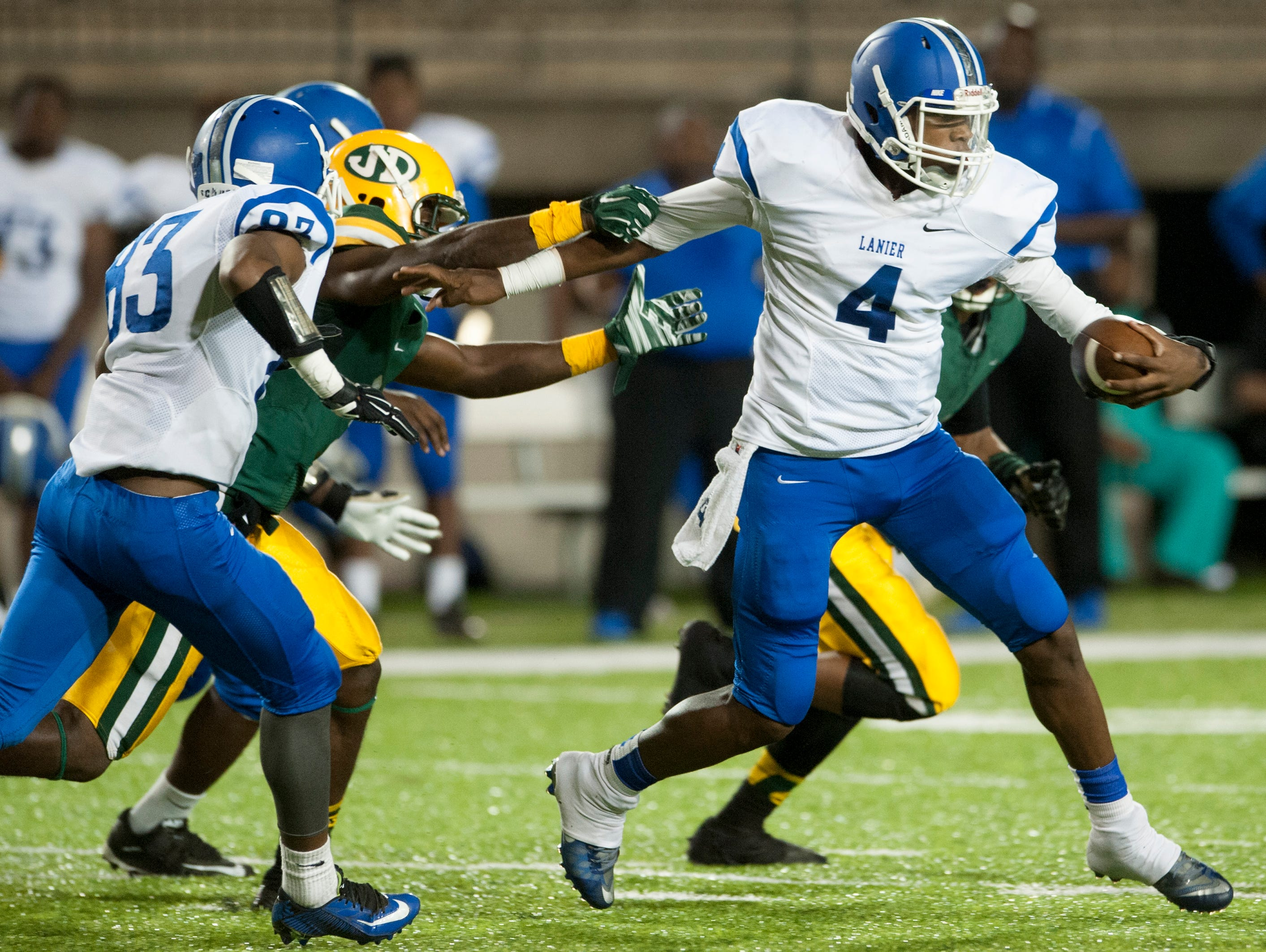 Lanier's James Foster tries to pull away from Jeff Davis defenders at Cramton Bowl in Montgomery, Ala. on Thursday September 24, 2015.