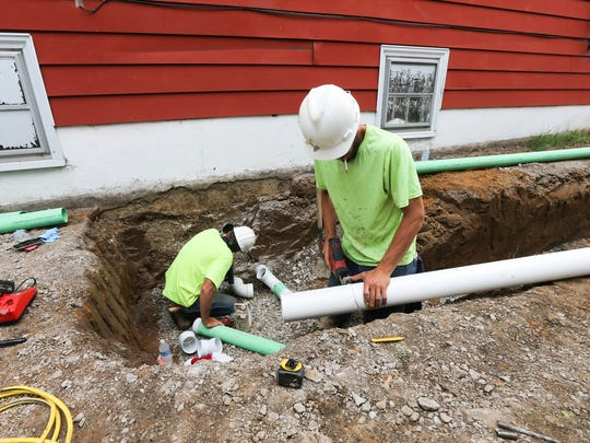 Nathan Wilson, right, cuts a section of pipe as he