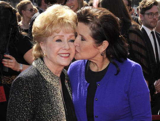 Carrie Fisher kisses her mother, Debbie Reynolds, as