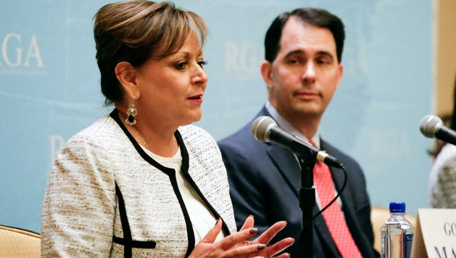 New Mexico Gov. Susana Martinez, left, speaks during a news conference while Wisconsin Gov. Scott Walker looks on, at the Republican Governors Association annual conference, Tuesday, Nov. 15, 2016, in Orlando, Fla. (AP Photo/John Raoux)
