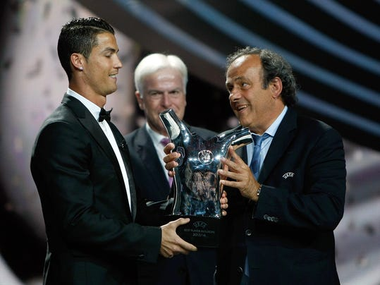 UEFA President Michel Platini, right, gives the trophy for best player of the year to Real Madrid Portuguese forward Cristiano Ronaldo, during the UEFA Champions League draw, at the Grimaldi Forum, in Monaco, Thursday, Aug. 28, 2014. (AP Photo/Claude Paris)
