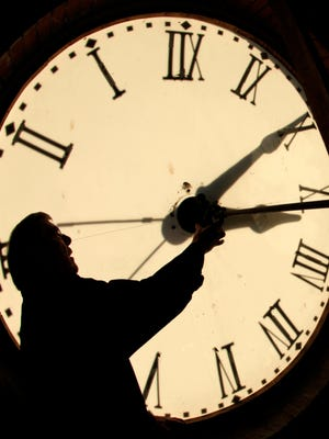 Custodian Ray Keen checks the time on a clock face Nov. 6, 2010, in Clay Center, Kan. Arizonans say to heck with that and keep their clocks on Mountain Standard Time all year.