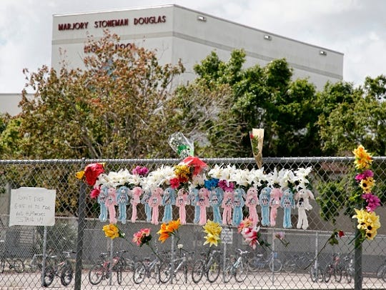 Memorials are seen on a fence surrounding Marjory Stoneman Douglas High School in Parkland, Florida, on Feb. 21, 2018, a week after a gunman killed 17 people.
