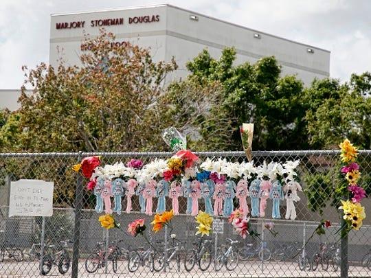 Memorials are seen on a fence surrounding Marjory Stoneman Douglas High School in Parkland, Florida on Feb. 21, 2018.