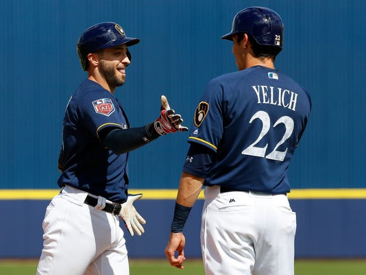 Milwaukee Brewers' Ryan Braun (8) high-fives Christian Yelich (22) after hitting a grand slam against the Chicago White Sox during the second inning of a spring training baseball game Wednesday, March 14, 2018, in Phoenix. (AP Photo/Matt York)