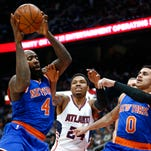 New York Knicks forward Quincy Acy (4) pulls down a rebound in front of Atlanta Hawks guard Kent Bazemore (24) as Shane Larkin (0) watches during the first half of an NBA basketball game Monday, April 13, 2015, in Atlanta. The Knicks won 112-108.