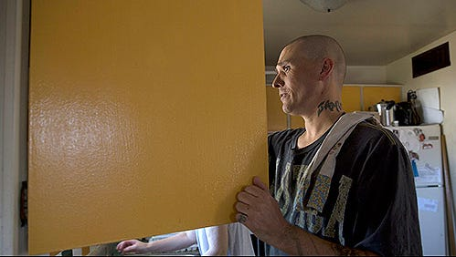 Brian Parker does chores in his kitchen in Tucson. The father of four is rebuilding his life following an addiction that began with a prescription for pills after a motorcycle accident.