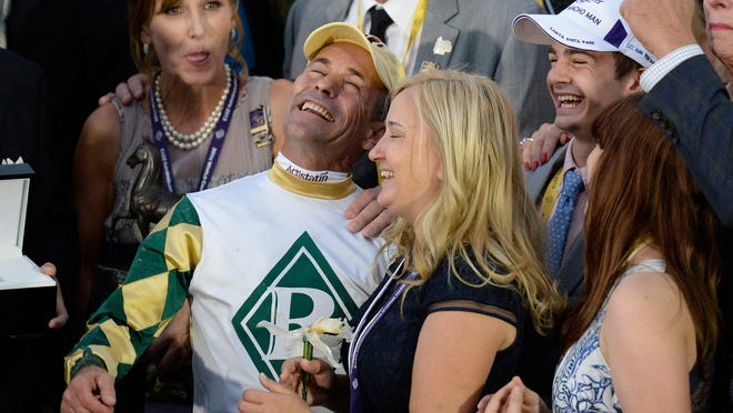Trainer Kathy Ritvo and jockey Gary Stevens celebrate Mucho Macho Man's victory in the $5 million Breeders' Cup Classic.