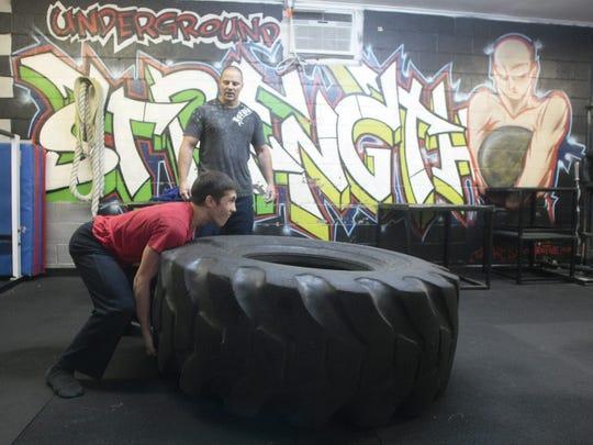 Zach Even-Esh (standing) spots a trainee during a workout
