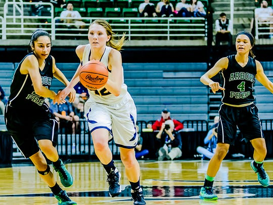 Kayla Belles ,center, of Ithaca dribbles out of a double-team