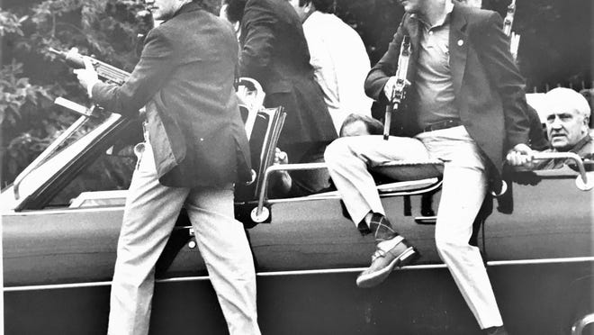 Secret Service agents swing into action after a man crashed his pickup through the gates of Augusta National Golf Club while President Ronald Reagan was playing golf.