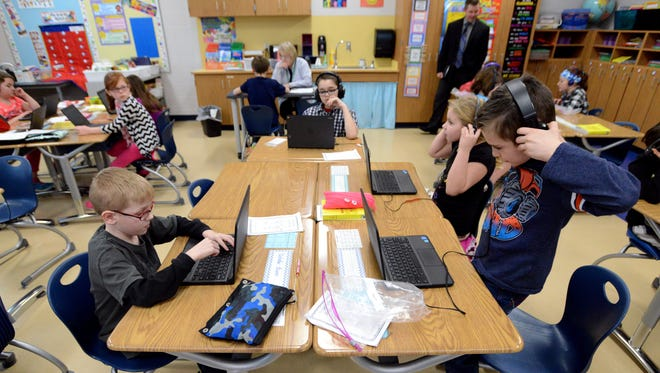 Talmadge Elementary School third grader Carson Rhymes, far right, puts on his headphones as he and his classmates (clockwise from lower left) Nicholas Beem, Cody Morgan and Denise Subler work on a reading lesson on their Google Chromebooks Wednesday, Feb. 15, 2017, in Lancaster.
