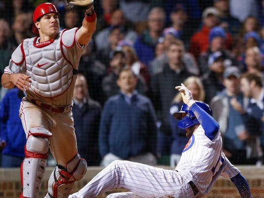 Chicago Cubs' Kris Bryant, right, scores as Philadelphia Phillies' J.T. Realmuto, left, waits for the ball during the ninth inning of a baseball game, Tuesday, May 21, 2019, in Chicago. (AP Photo/Kamil Krzaczynski)