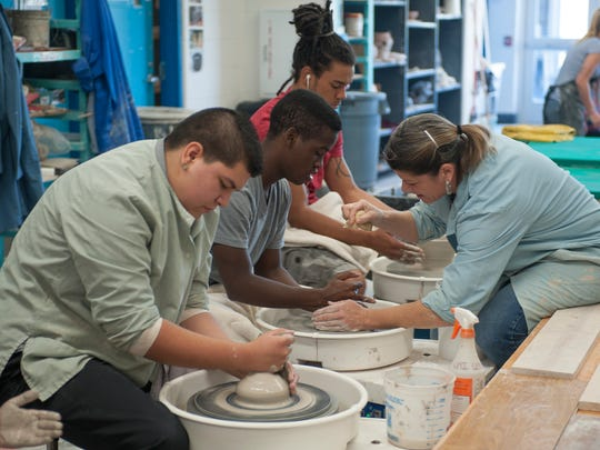 "USI's Alisa ""Al"" Holen works with a group from Bosse High School for the third annual Empty Bowls project."