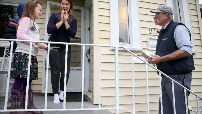 """Mail carrier Norm Hall sings a """" Happy Birthday """" song to Evangeline Hamon, 6, as her mom Julia reacts on his last day of work on his Manette route Friday. The Hamon's also gave him a retirement ."""