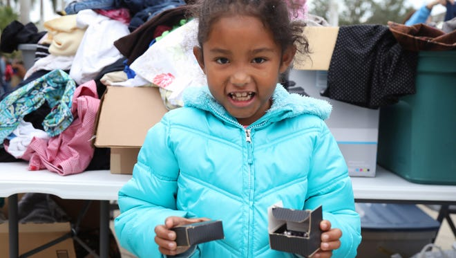 Kahlia Harris finds a pair of pretty purple earrings at Saturday's annual Homeless Service Day and Veteran Stand Down at City of Palms Stadium in Fort Myers.