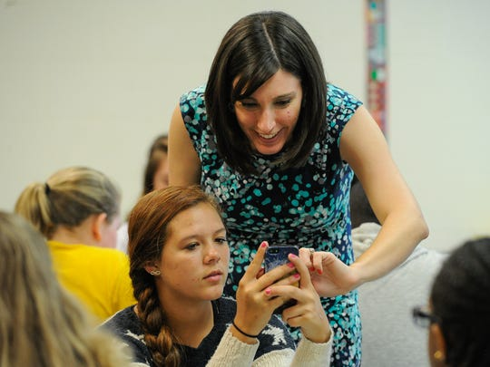 """Megan Szabo, Delaware's Teacher of the Year, helps Brianna Stevenson with her smartphone during a science lesson at Postlethwait Middle School in Camden. Megan has made her """"platform"""" finding ways to let students use their own smartphones, laptops and other tech in their classrooms."""