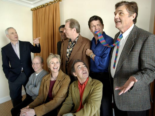 """FILE - In this March 21, 2003, file photo, the cast of the film """"The Mighty Wind,"""" standing from left, Christopher Guest, Eugene Levy, Michael McKean, John Michael Higgins, Fred Willard, and, seated, Bob Balaban, Jane Lynch, and Harry Shearer, amuse themselves during a photo shoot in Beverly Hills, Calif. Willard, the comedic actor whose improv style kept him relevant for more than 50 years in films like """"This Is Spinal Tap,"""" """"Best In Show"""" and """"Anchorman,"""" has died at age 86. Willard's daughter, Hope Mulbarger, said in a statement Saturday, May 16, 2020, that her father died peacefully Friday night. (AP Photo/Kevork Djansezian, File)"""