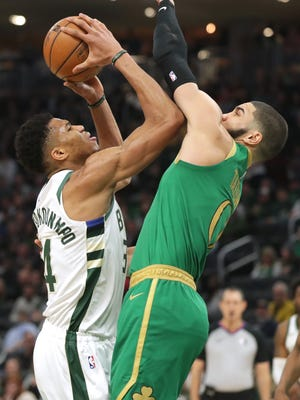Bucks forward Giannis Antetokounmpo, left, is fouled by Celtics forward Jayson Tatum during their January game in Milwaukee. The Celtics and Bucks will meet Friday night as the NBA season resumes in Florida.