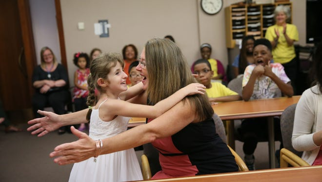 Abby Novotny, 10, runs to hug her adoptive mom, Anne Novotny, after a judge made the adoption official Monday. Her classmates from St. Coletta Day School and family and friends watch from around the courtroom of Judge Christopher Foley.