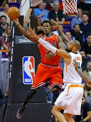 Chicago Bulls guard Jimmy Butler (21) passes behind Phoenix Suns center Tyson Chandler during the first half of their NBA game Wednesday, Nov. 18, 2015 in Phoenix.