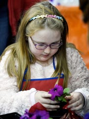 Mackenzie Sartre, 9, planting a petunia at the Lowes booth during last year's Heritage Federal Credit Union Home Show. This year's show is back Saturday and Sunday.