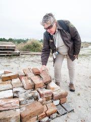 Park volunteer Anne Weeks points out recycled bricks