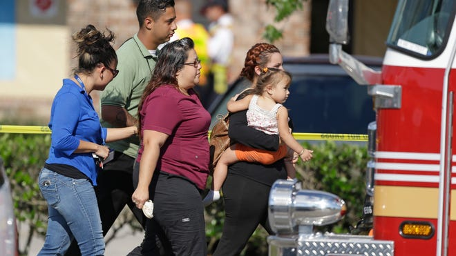 Parents and relatives leave a KinderCare Learning Center in Orlando on April 9, 2014, after a vehicle hit by an SUV crashed into the day care center. Authorities said 12 children and three adults were injured.