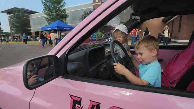 Cousins James Riedlinger, 3, and Elsie Schornstein, 3, pretend to drive a truck provided by Eastgate Towing during family night at the 20th annual Hot Harley Nights at J&L Harley-Davidson on Thursday. The event supports Make-A-Wish¨ South Dakota and continues through the weekend.