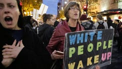 "A woman holds a sign reading ""White People Wake Up"""
