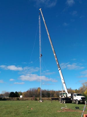 A crane raises a 120-foot-tall tower in Nasewaupee on Thursday for Door County Broadband LLC. The company erected two towers there this week to begin providing its Internet services to southern Door County.