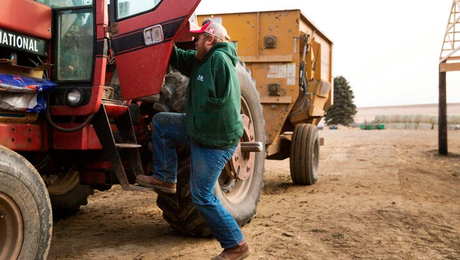 Kyle Lammers climbs into his tractor to feed cattle Friday, Jan 19, 2018, in Hartington, Neb. In November of 1998, Lammers lost his left arm in a farming accident when he was 13 years old.