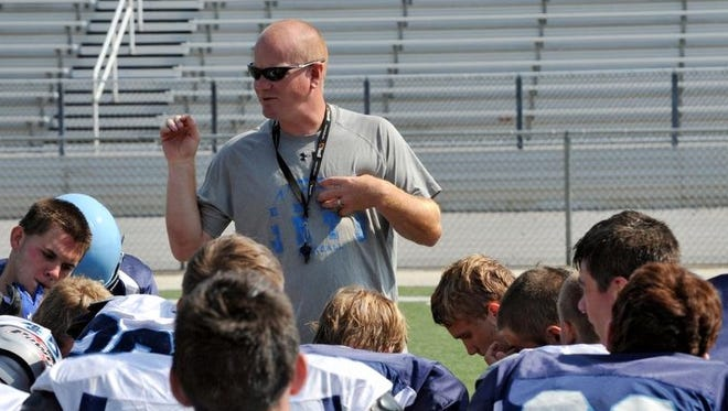Enka football coach Jeff Frady addresses his players at the conclusion of Wednesday's practice in Candler.
