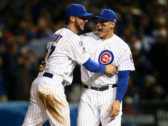 Chicago Cubs third baseman Kris Bryant (17) and first baseman Anthony Rizzo (44) celebrate the 6-4 victory and against St. Louis Cardinals in game four of the NLDS at Wrigley Field.