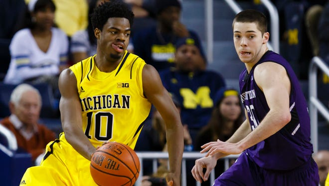 Michigan guard Derrick Walton Jr. (10) moves the ball against Northwestern Wildcats guard Bryant McIntosh.