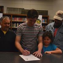 Yellville-Summit basketball standout Jacob Berry, middle, signed a National Letter of Intent on Friday at the high school library, to play at Crowley's Ridge College in Paragould.