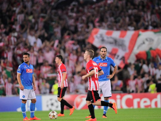 SSC Napoli's Gonzalo Higuain, right, laments after his team lose their match 3-1 against Athletic Bilbao,  during their Champions League playoff second leg soccer match, at San Mames stadium in Bilbao, northern Spain, Wednesday, Aug. 27, 2014.(AP Photo/Alvaro Barrientos)