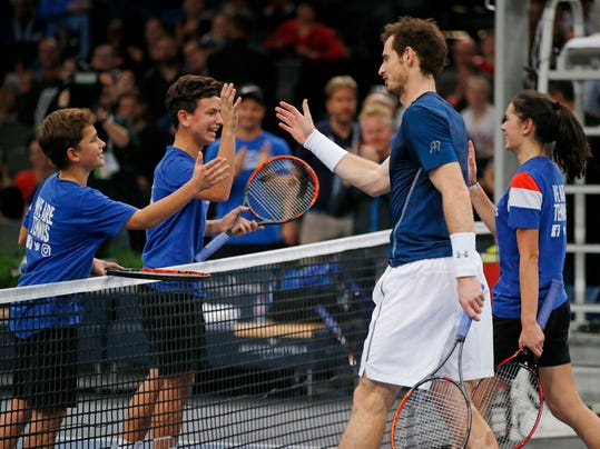 Britain's Any Murray shakes hands with ball boys and a ball girl after he played with them during a training session at the Paris Masters tennis tournament at the Bercy Arena in Paris, Saturday, Nov. 5, 2016.. Andy Murray becomes world tennis No. 1 after Milos Raonic walkover in Paris. (AP Photo/Michel Euler)