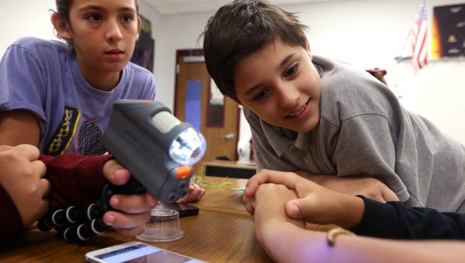 Magee Elementary School fifth-graders McKensly Brietzke, 11 (left), and Dominick Estrada, 10, use a handheld Wi-Fi microscope in their classroom last week. The microscopes were purchased by Magee Elementary using a $25,000 grant sponsored by the America's Farmers Grow Rural Education Program Monsanto Fund.