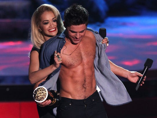 Rita Ora, left, rips open Zac Efron's shirt as he accepts the award for best shirtless performance for ?That Awkward Moment? on stage at the MTV Movie Awards on Sunday, April 13, 2014, at Nokia Theatre in Los Angeles. (Photo by Matt Sayles/Invision/AP)