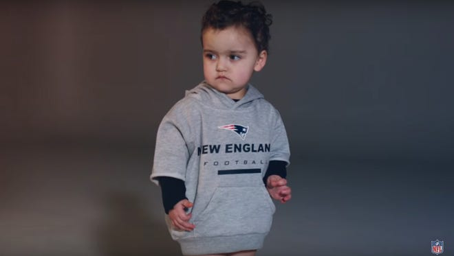 A baby dressed like Bill Belichick for an NFL Super Bowl ad.