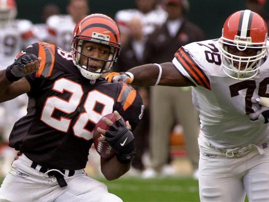 Cincinnati Bengals' Corey Dillon tries to escape the