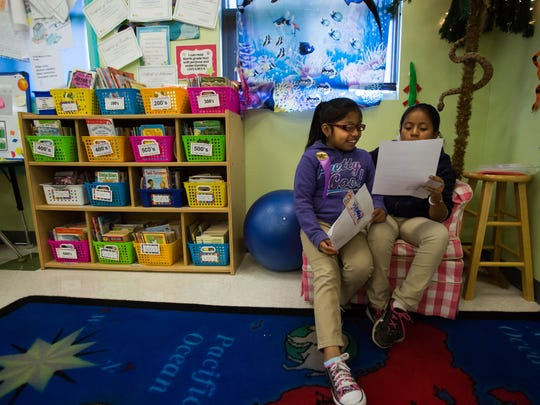 Angelica Garcia-Loarca, 9, left, and Kaely Perez-Tomas, 10, right, share their pen pal letters with each other at Immokalee Community School January 23rd, 2017. The teacher, Ann Marie Morgiewicz, covers the classroom windows in case she ever needs to hide her students from a shooter.