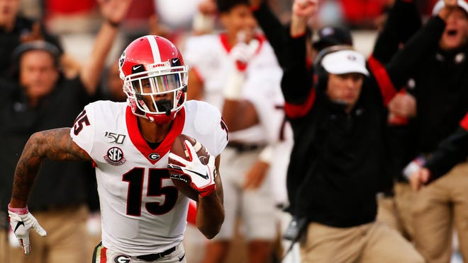 Georgia wide receiver Lawrence Cager (15) drives in for a touchdown as Georgia coach Kirby Smart celebrates at background right during the second half against Florida in an NCAA college football game Saturday, Nov. 2, 2019, in Jacksonville, Fla. (Joshua L. Jones/Athens Banner-Herald via AP)