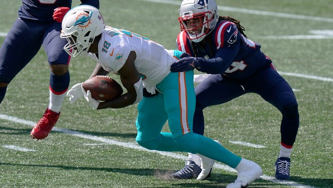 New England Patriots cornerback Stephon Gilmore, right, tackles Miami Dolphins wide receiver Preston Williams in the first half of an NFL football game, Sunday, Sept. 13, 2020, in Foxborough, Mass.
