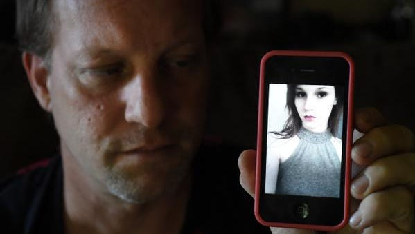 Jason Glaze holds up a cellphone photo of his missing daughter, Olivia Ann Glaze, last week. Glaze announced in a Facebook post that he spoke to his daughter Tuesday, confirming her safety.