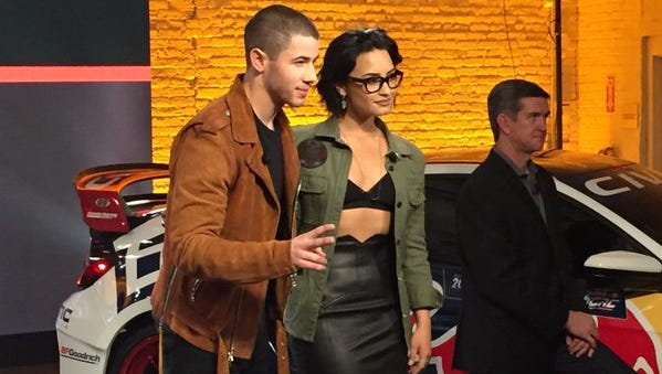 Celebrity artists Nick Jonas and Demi Lovato promote their upcoming concert tour for Honda at an event tied to the New York International Auto Show.