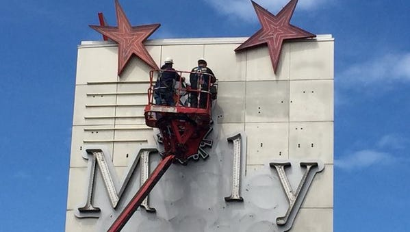 Workers remove Medley Centre sign elements.