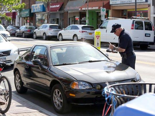 A parking enforcement officer prints out a parking