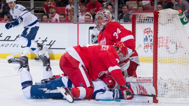 Detroit left wing Justin Abdelkader falls on top of Tampa Bay right wing J.T. Brown.